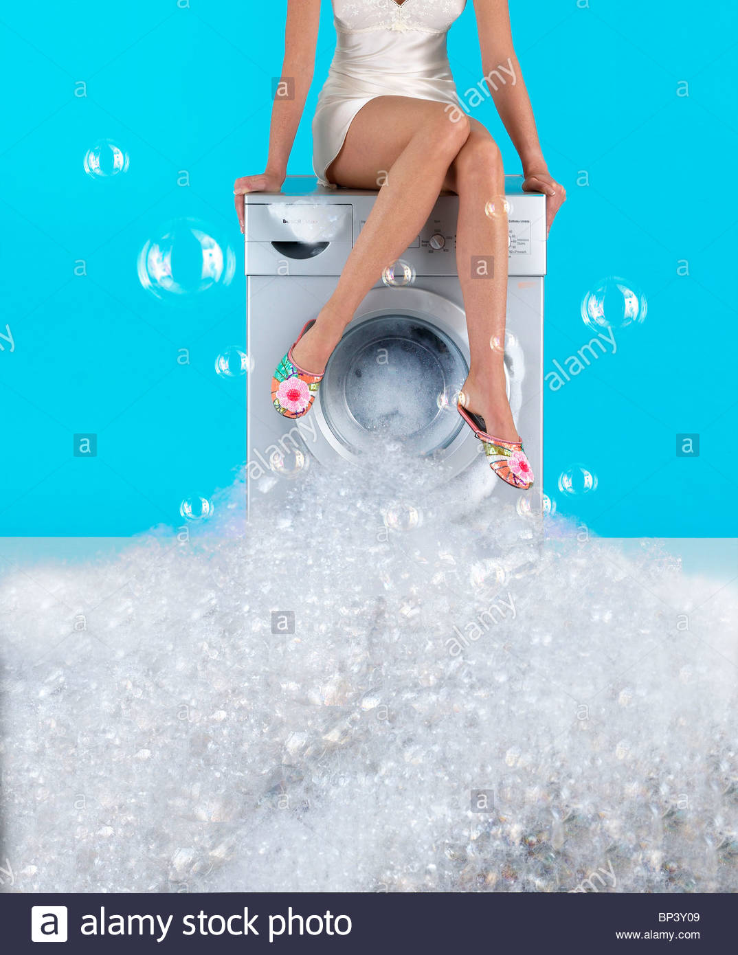A Woman Sits On A Washing Machine That Is Overflowing With