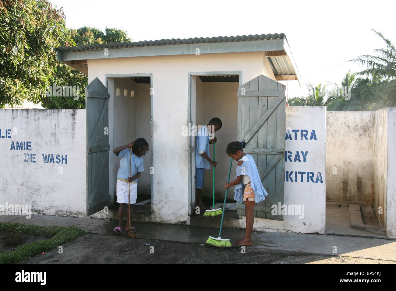 Children clean the latrines at school as part of water and ...