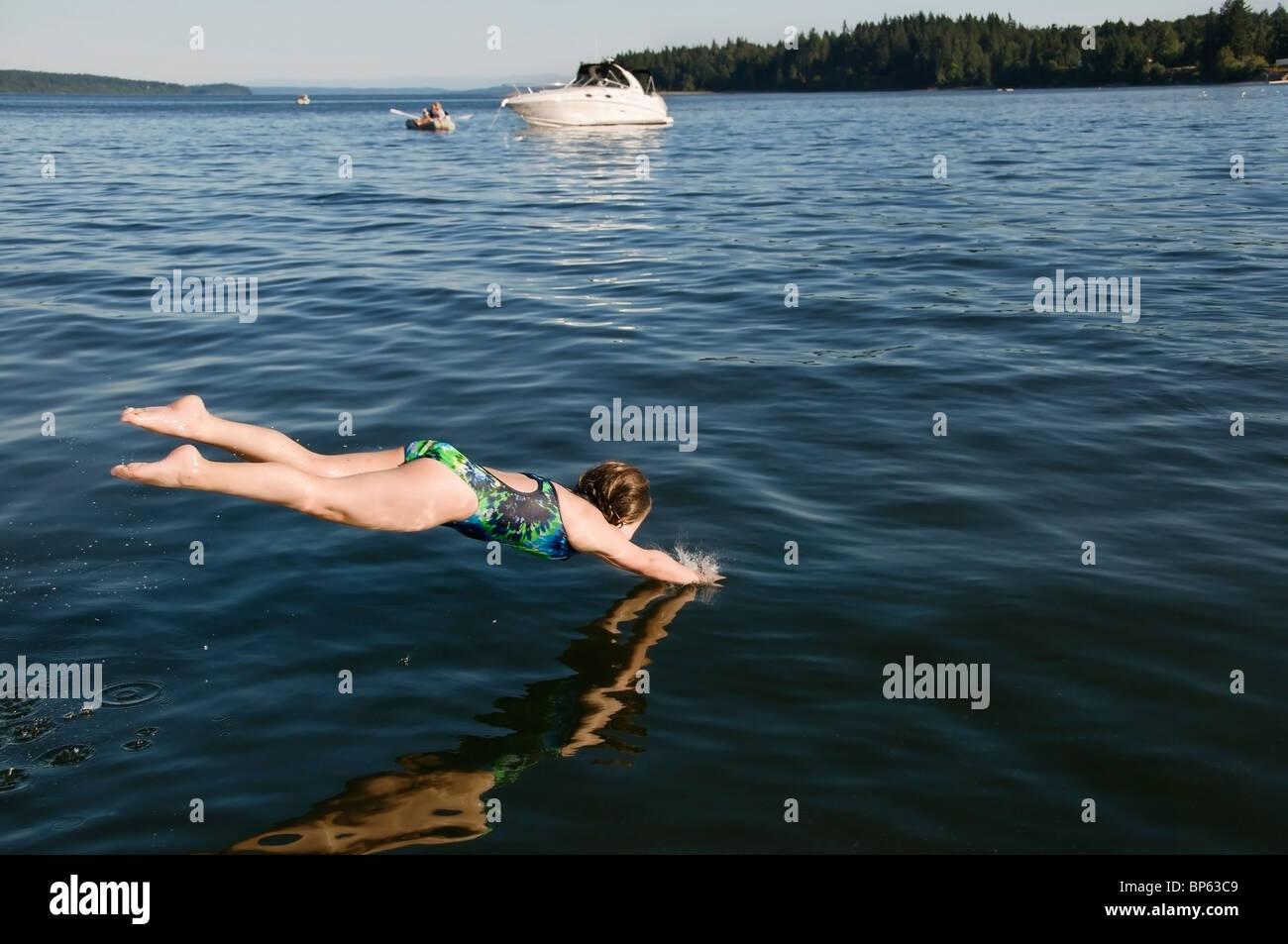 A Girl Dives Head First Into The Cold Water Of South Puget