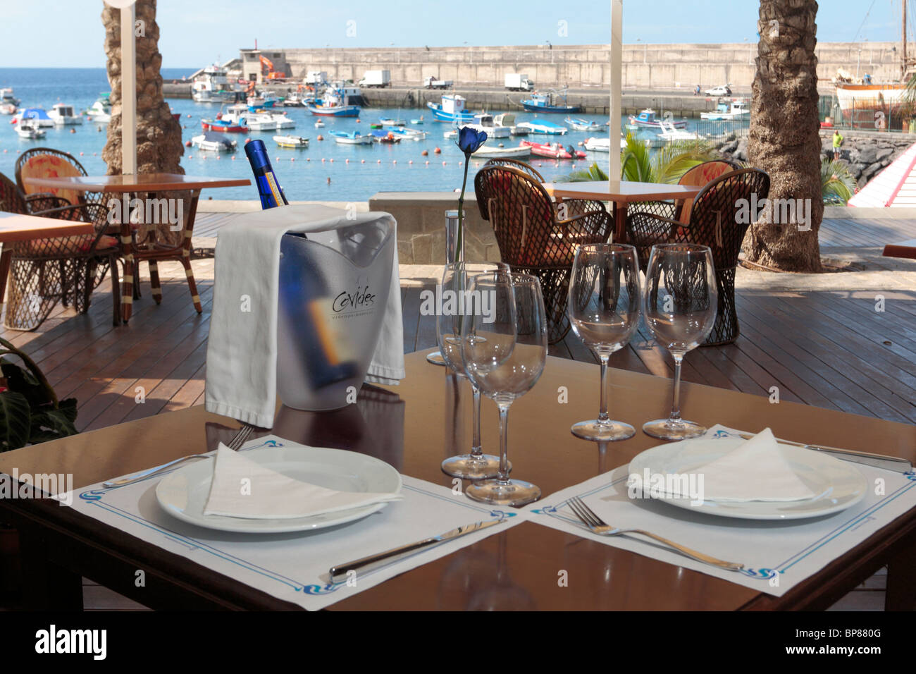 a restaurant table set for two on a terrace overlooking the port at stock photo royalty free. Black Bedroom Furniture Sets. Home Design Ideas