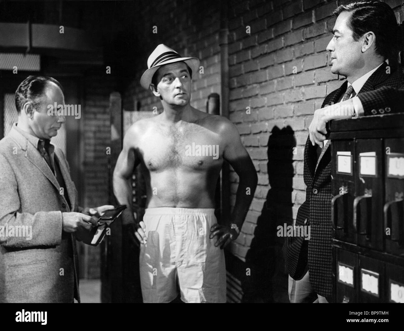 Mitchum agrees to a strip search before Martin Balsam and Gregory Peck. He's been lifting.