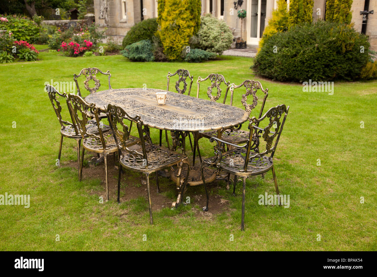 Colored cast - Old Fashioned Gold Colored Cast Iron Table And Eight Chairs On Formal Lawn