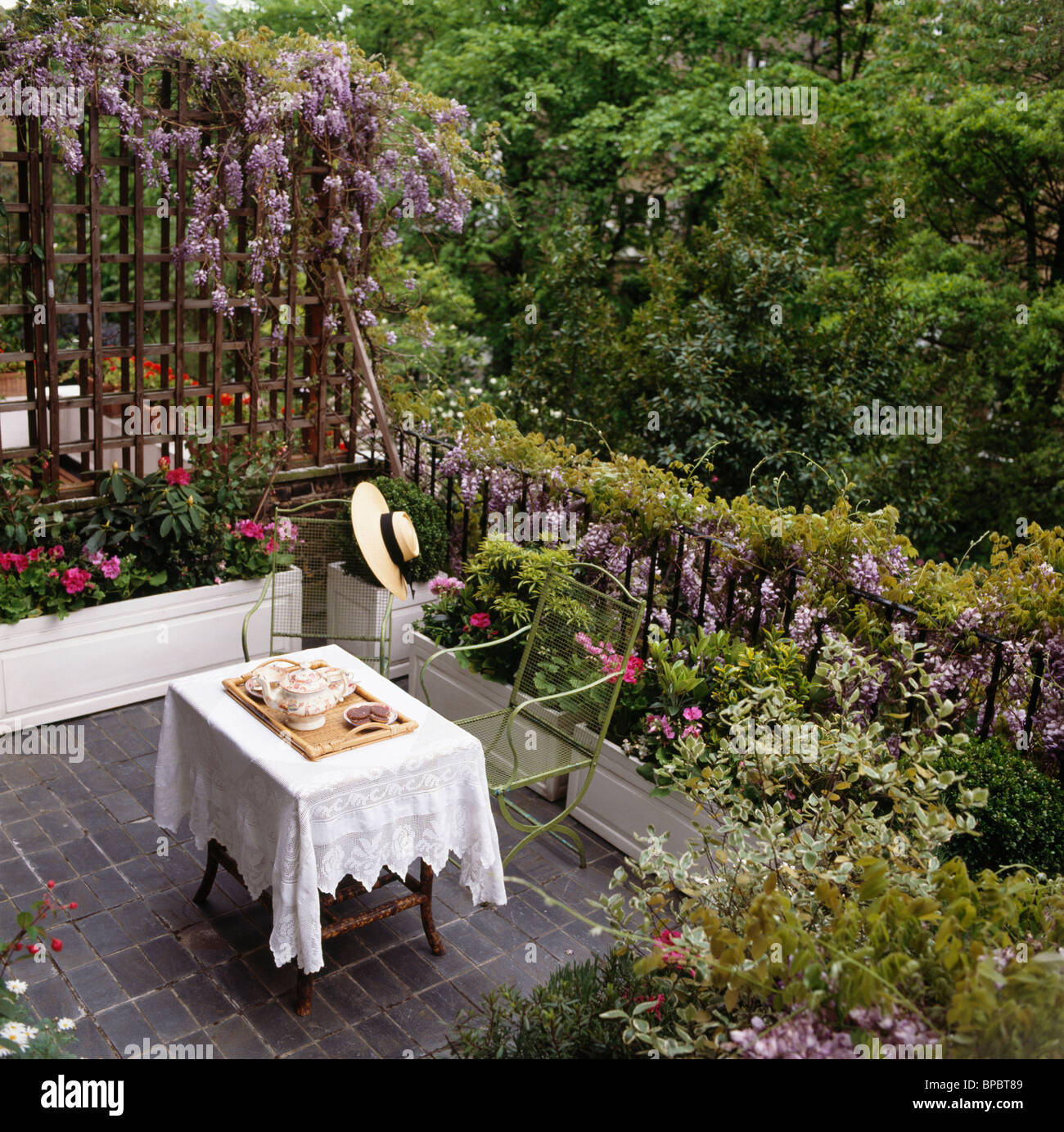 small balcony table looking down on small paved balcony with wisteria on trellis and railings above balcony furnished small foldable
