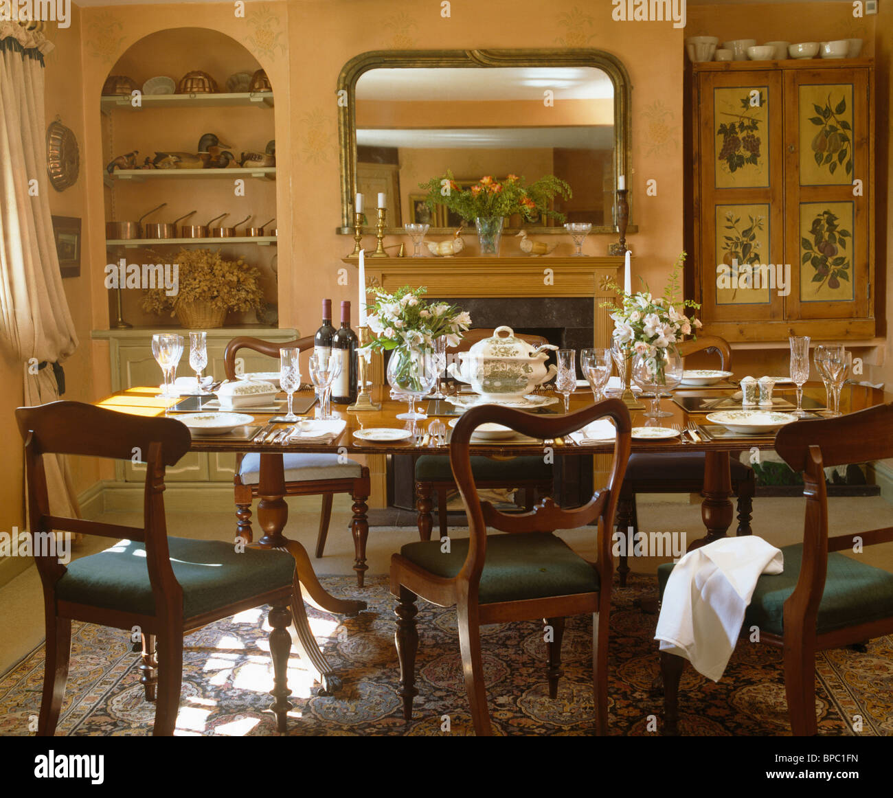 Antique Chairs At Table Set For Lunch In Country Dining Room With Large Mirror Above Fireplace And Alcove Shelving