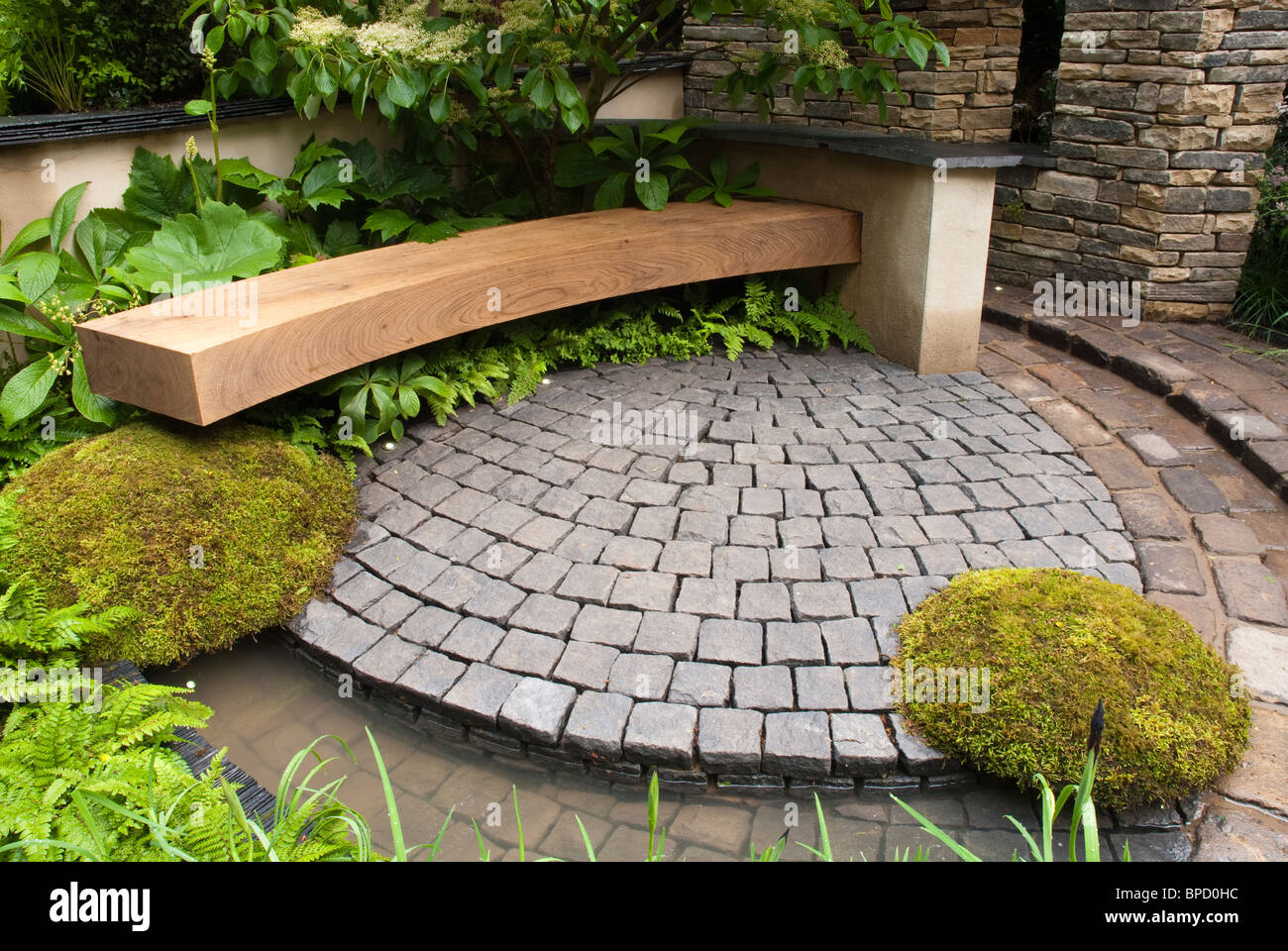 Garden Bench And Stone Patio In Circular Curves With Moss