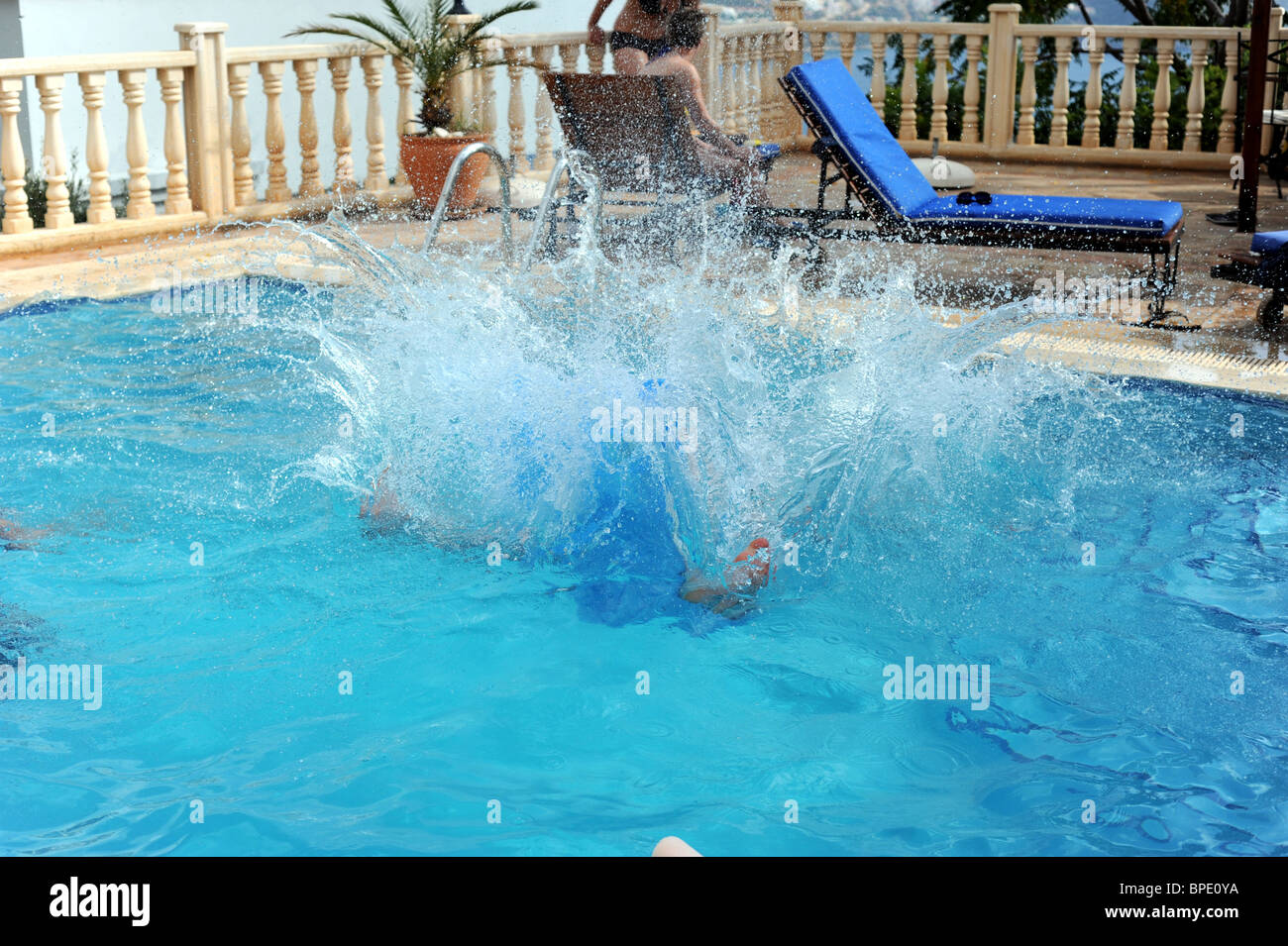 a man makes a huge splash as he jumps into the holiday villa swimming stock photo royalty free