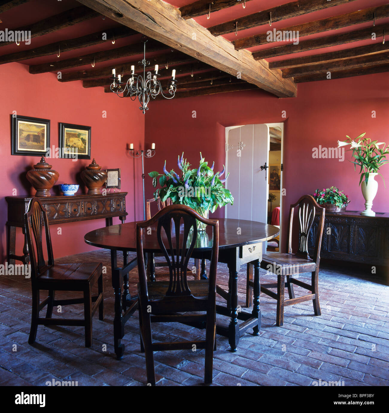 Antique Oak Table And Chairs In Dark Pink Country Dining Room With Old Brick  Flooring And Wood Beamed Ceiling