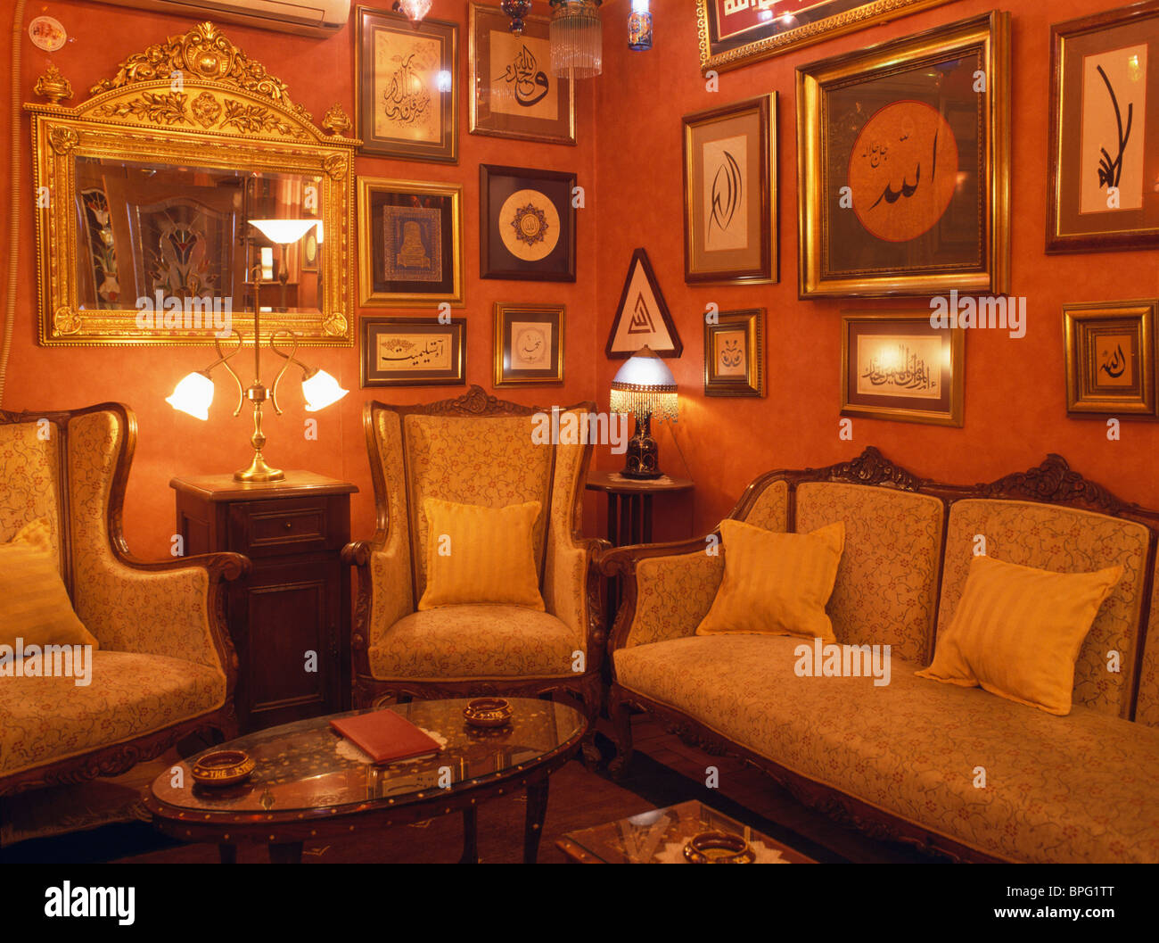 Pictures Covering Walls Of Red Turkish Living Room With Traditional Sofa  And Armchairs And Lighted Lamps