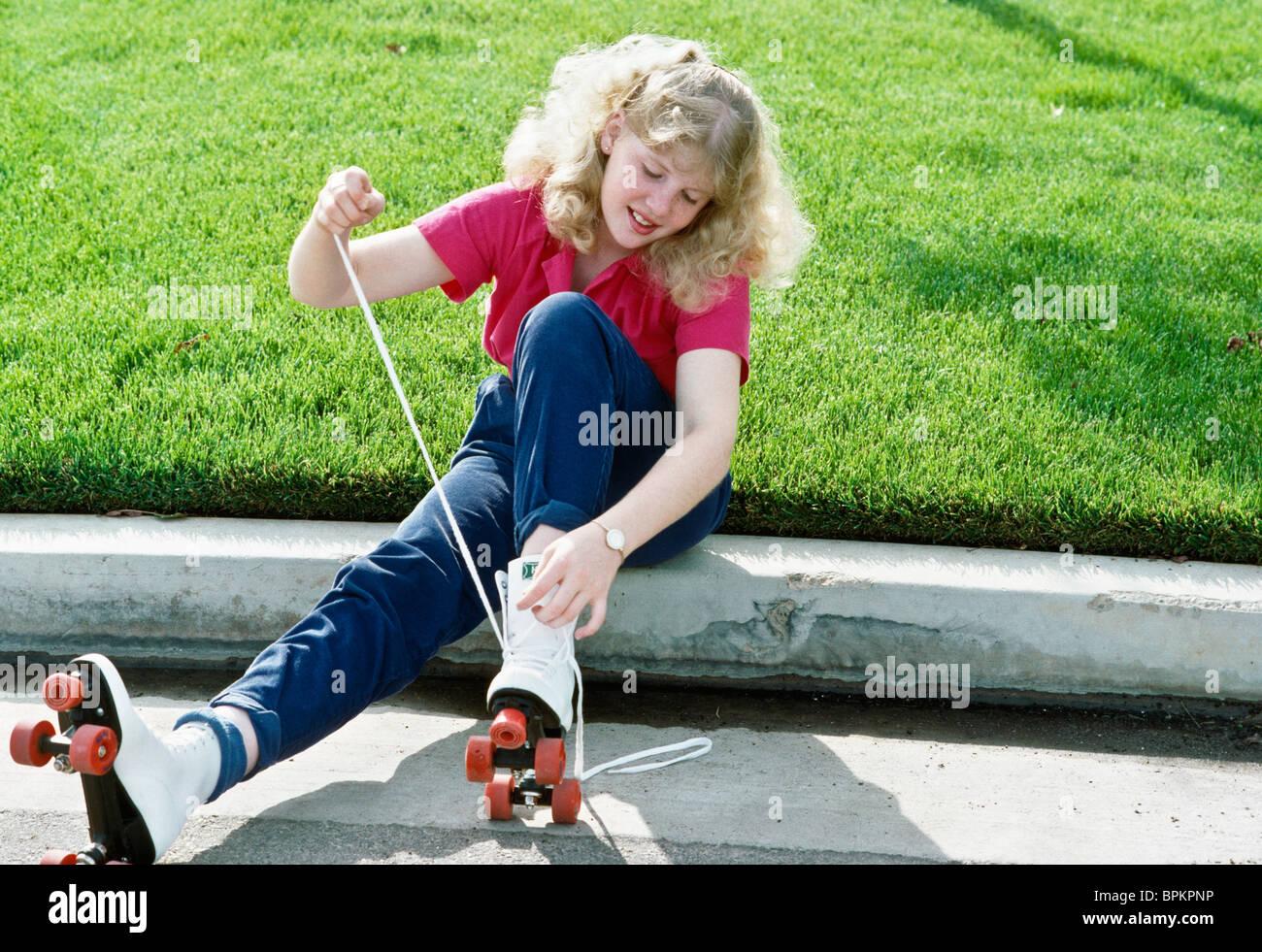 Roller skates winnipeg - Teenage Girl Lacing Up Roller Skates Stock Image