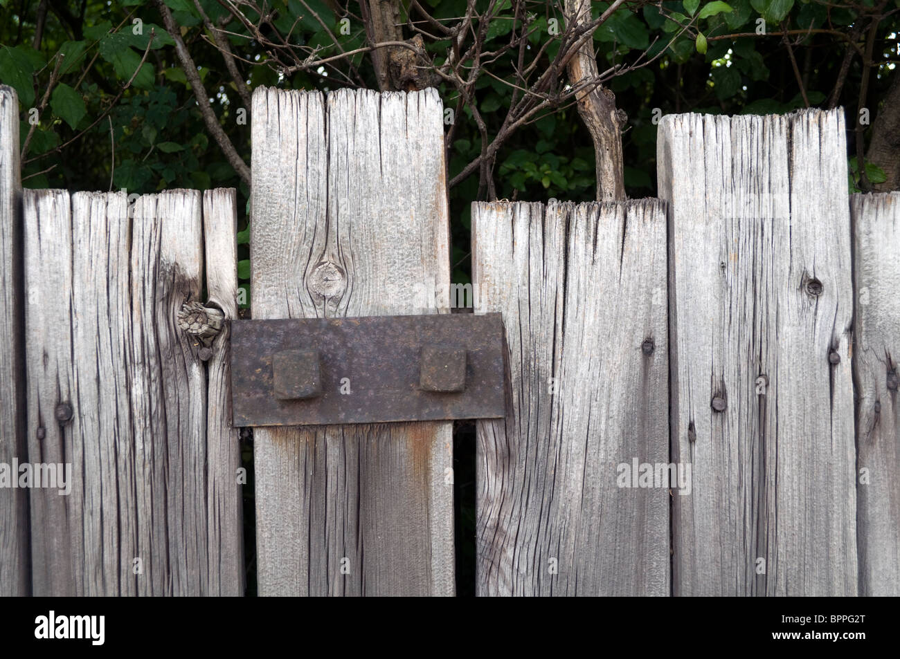 A Rickety Old Wooden Fence Reinforced And Repaired With A