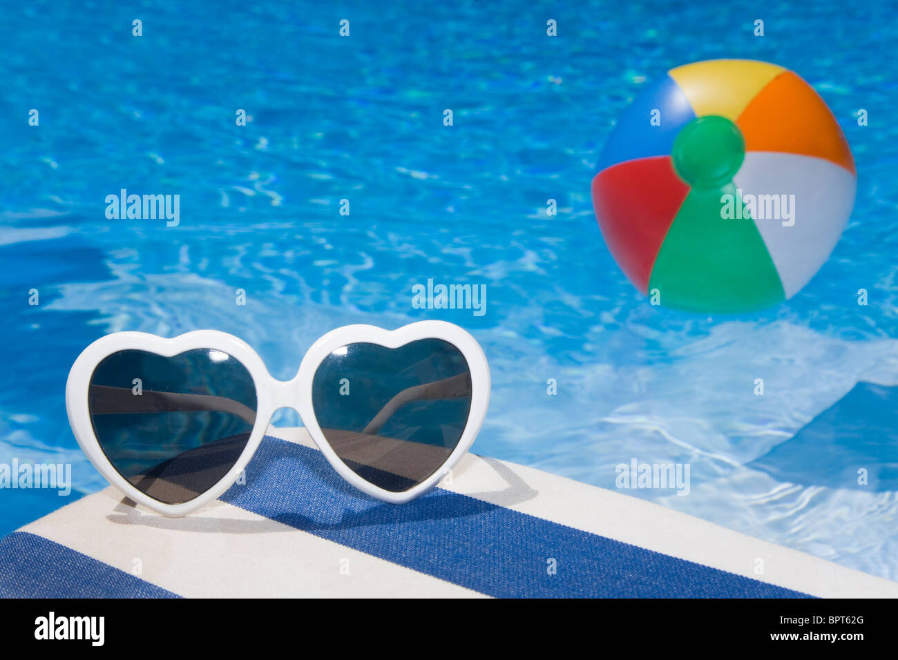 Heart Shaped Sunglasses By A Blue Swimming Pool