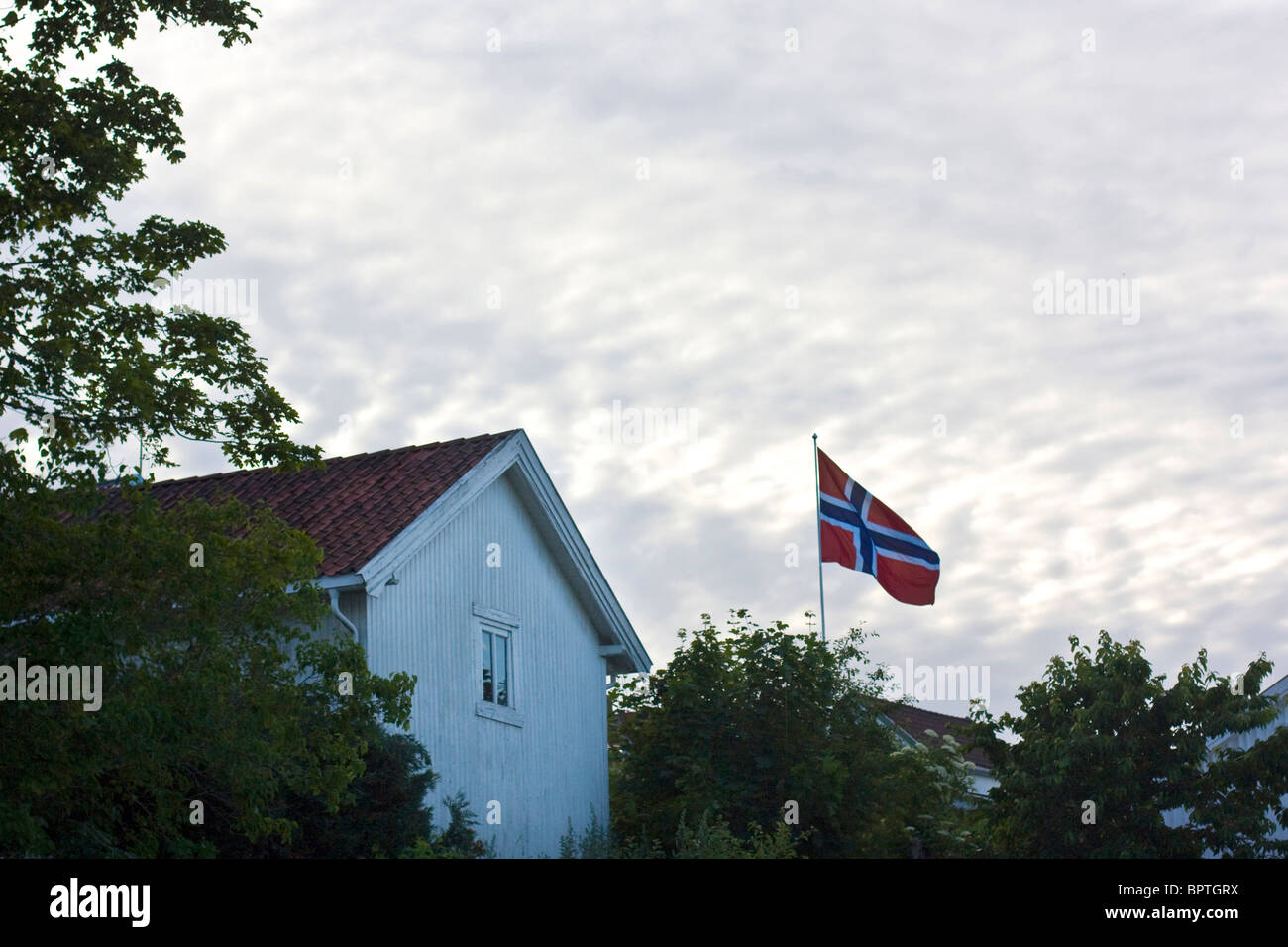 a norwegian flag flying outside a house in asgardstrand norway