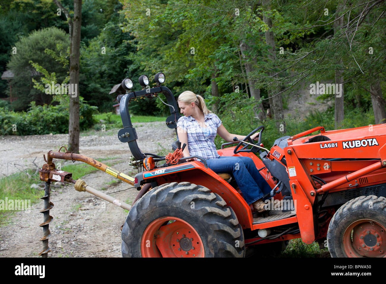 Kubota tractors for sale in kentucky - Young Blond Woman Driving Kubota Tractor With Post Hole Digger Attachment Working On Farm Stock