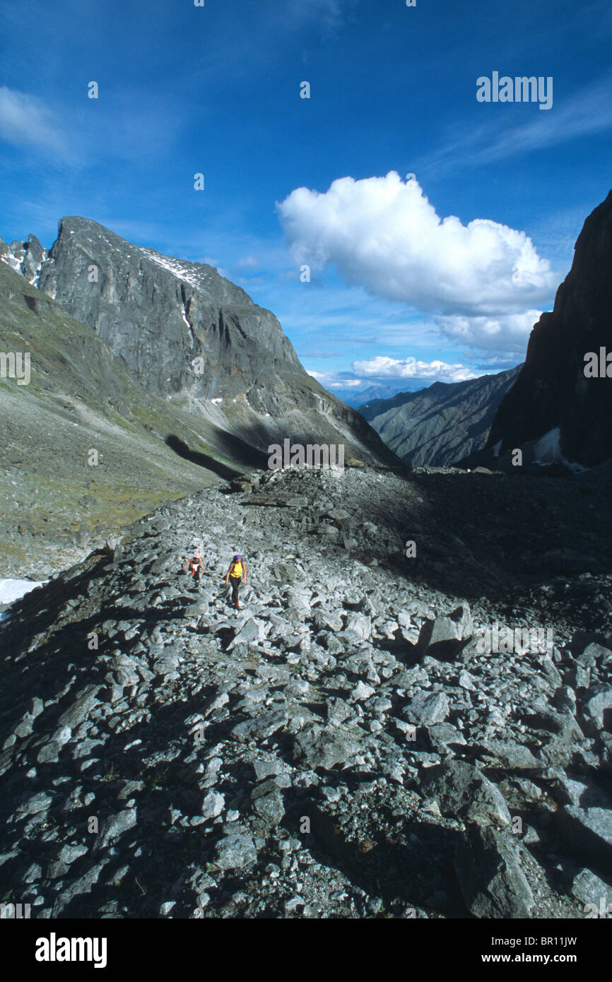Two female hikers cross the moraine below the lotus flower tower in two female hikers cross the moraine below the lotus flower tower in the cirque of the unclimbables in canadas northwest territo izmirmasajfo Image collections