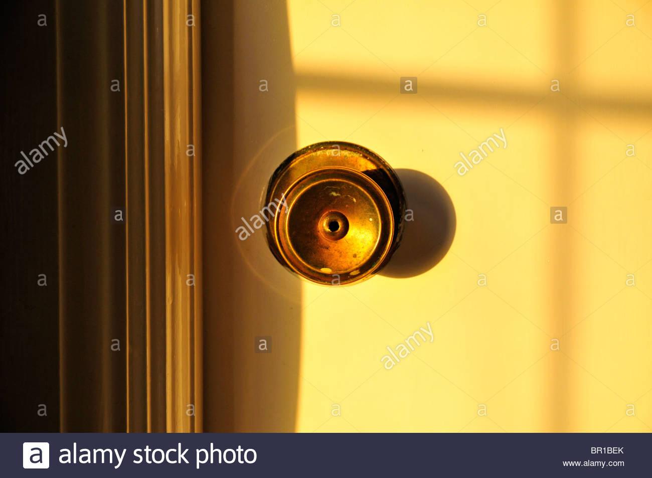 round brass door knob with key lock cast in strong sunlight shadow