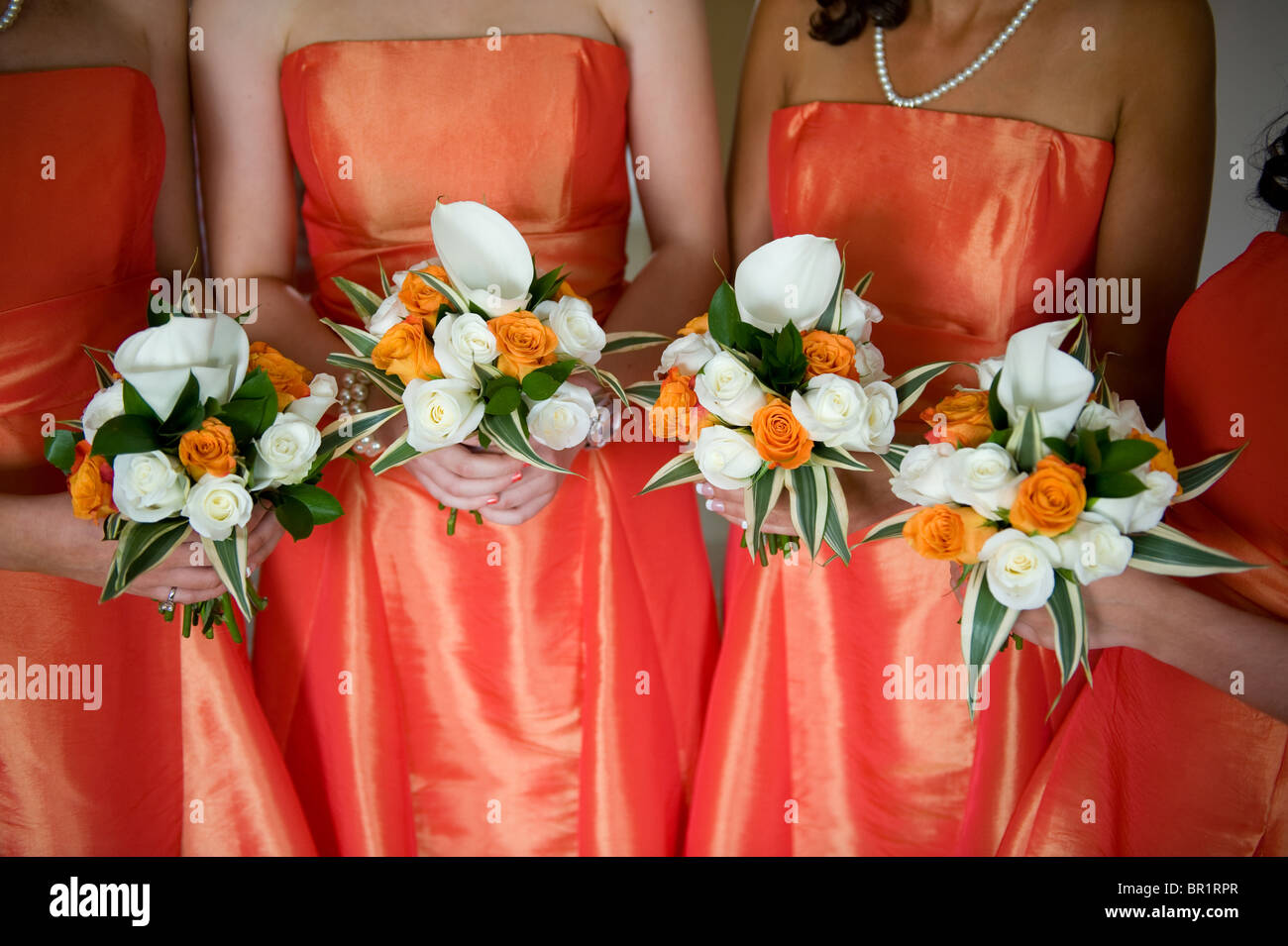 Bridesmaids Holding Wedding Bouquets Of Orange And White Roses Lilies