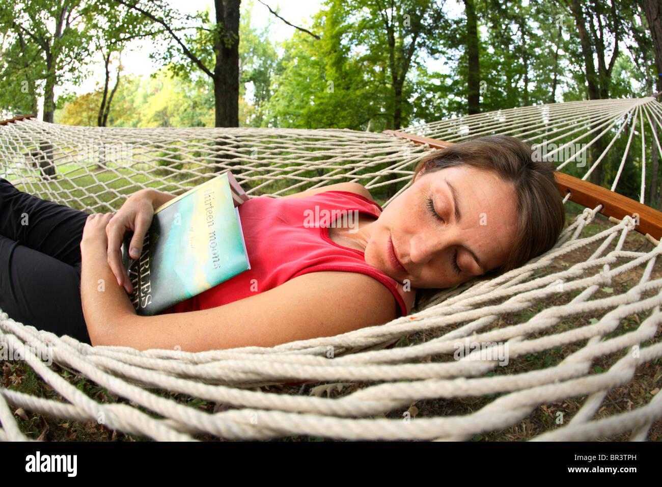 young woman falls asleep while reading a good book in a hammock in