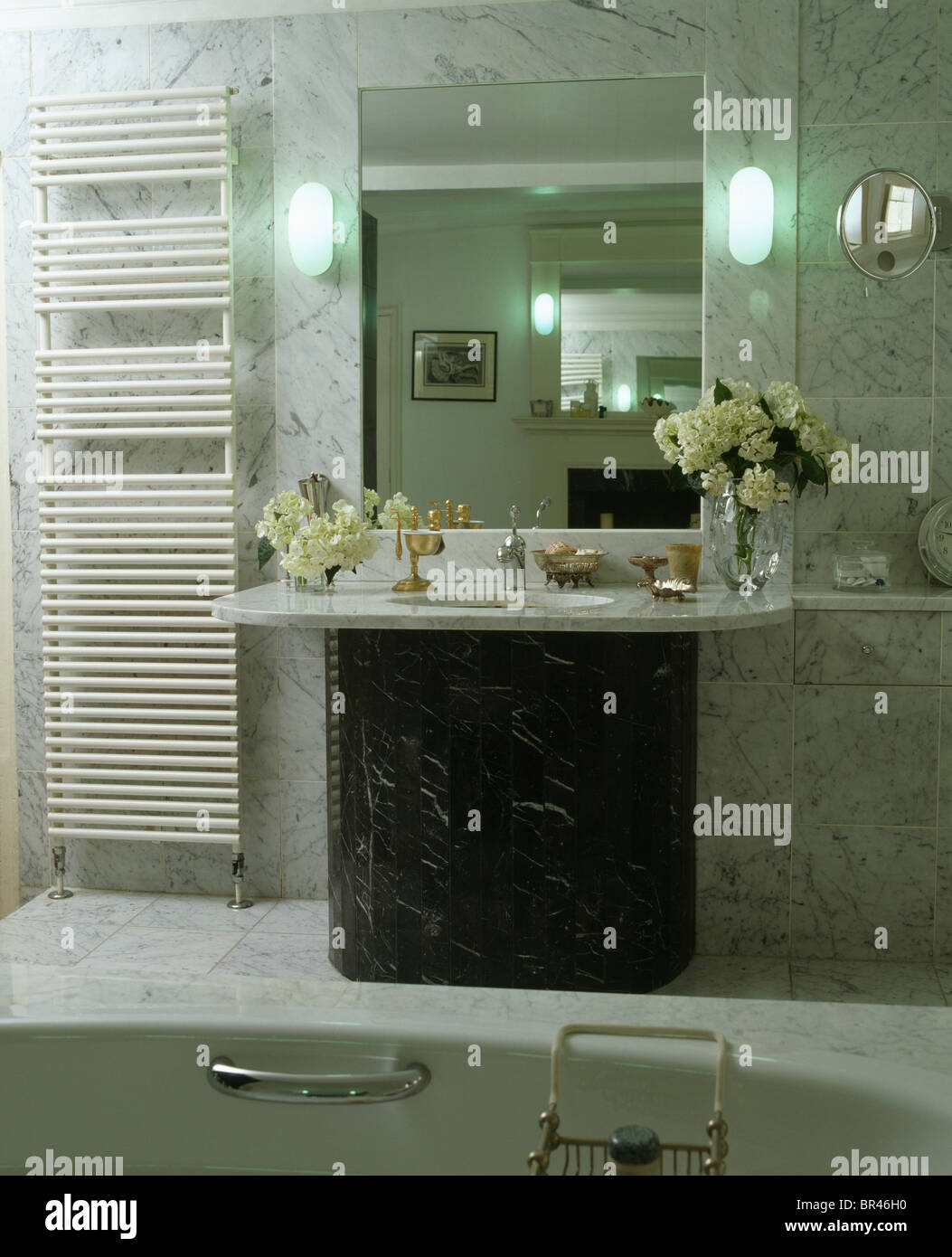 Wall-lights on either side of mirror above marble-topped vanity ...