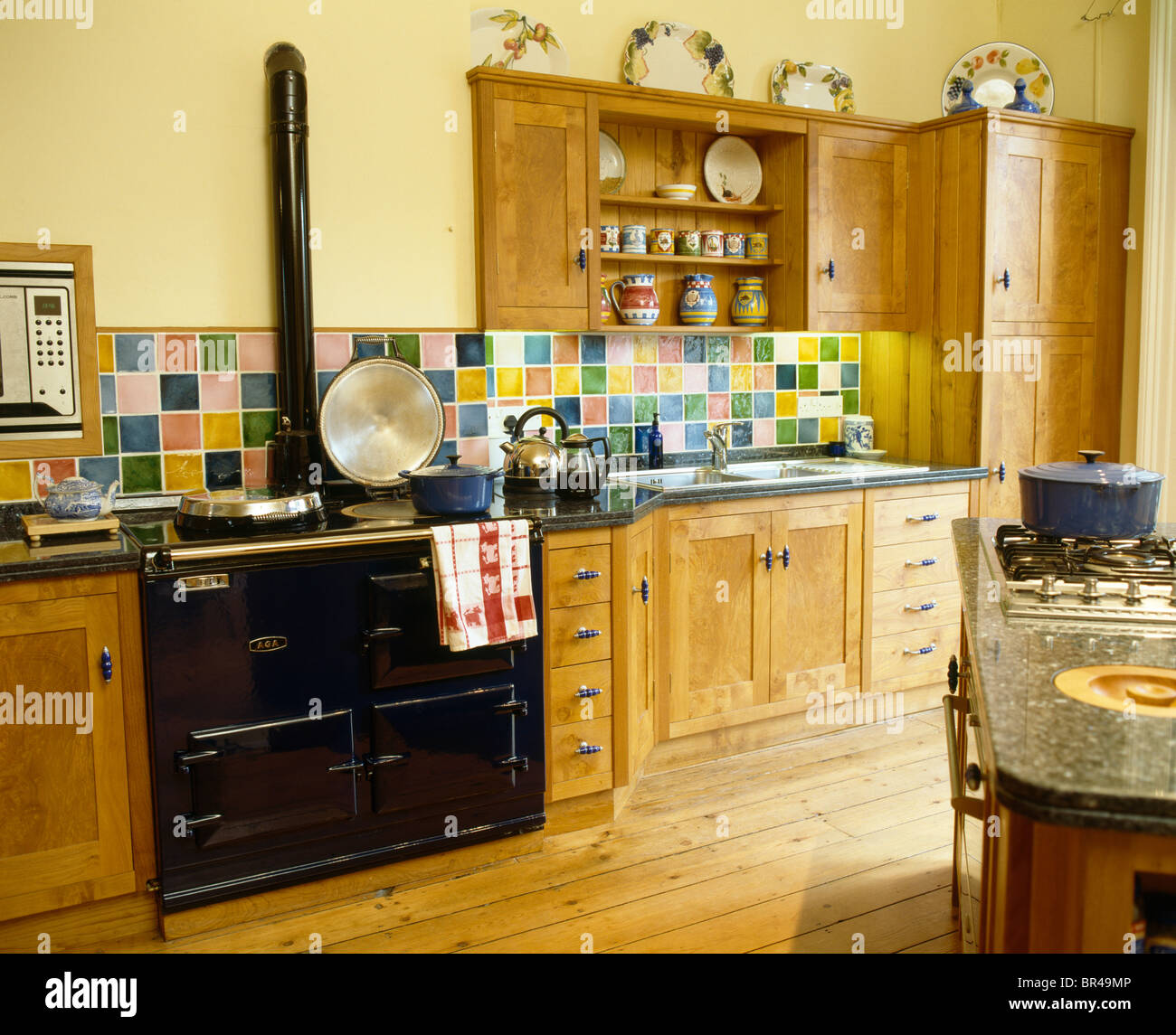 Multi colored ceramic tiles on wall above black aga oven in stock multi colored ceramic tiles on wall above black aga oven in traditional yellow kitchen with wooden fitted units dailygadgetfo Choice Image