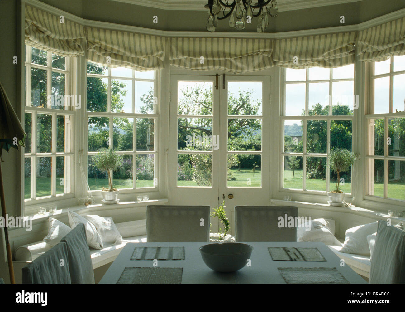 Striped blinds on french windows in dining room with view for Garden room windows