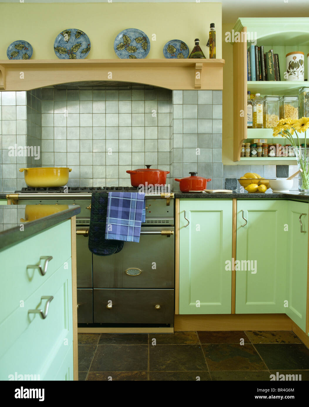 Green country kitchen - Pale Gray Tiles On Wall Above Green Range Oven In Country Kitchen With Pale Green Fitted Units