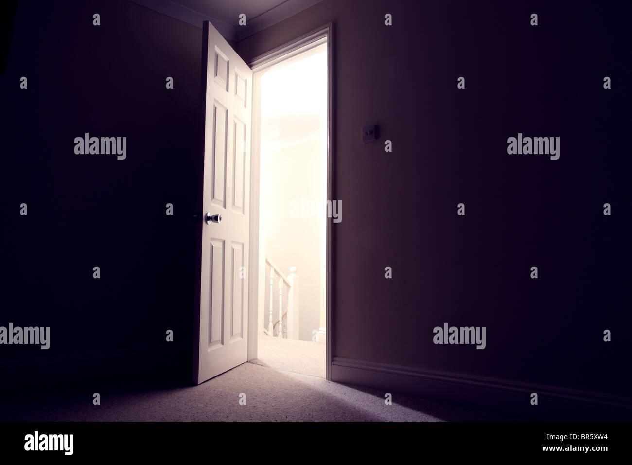 Dark room with open door light streaming in Stock Photo Royalty