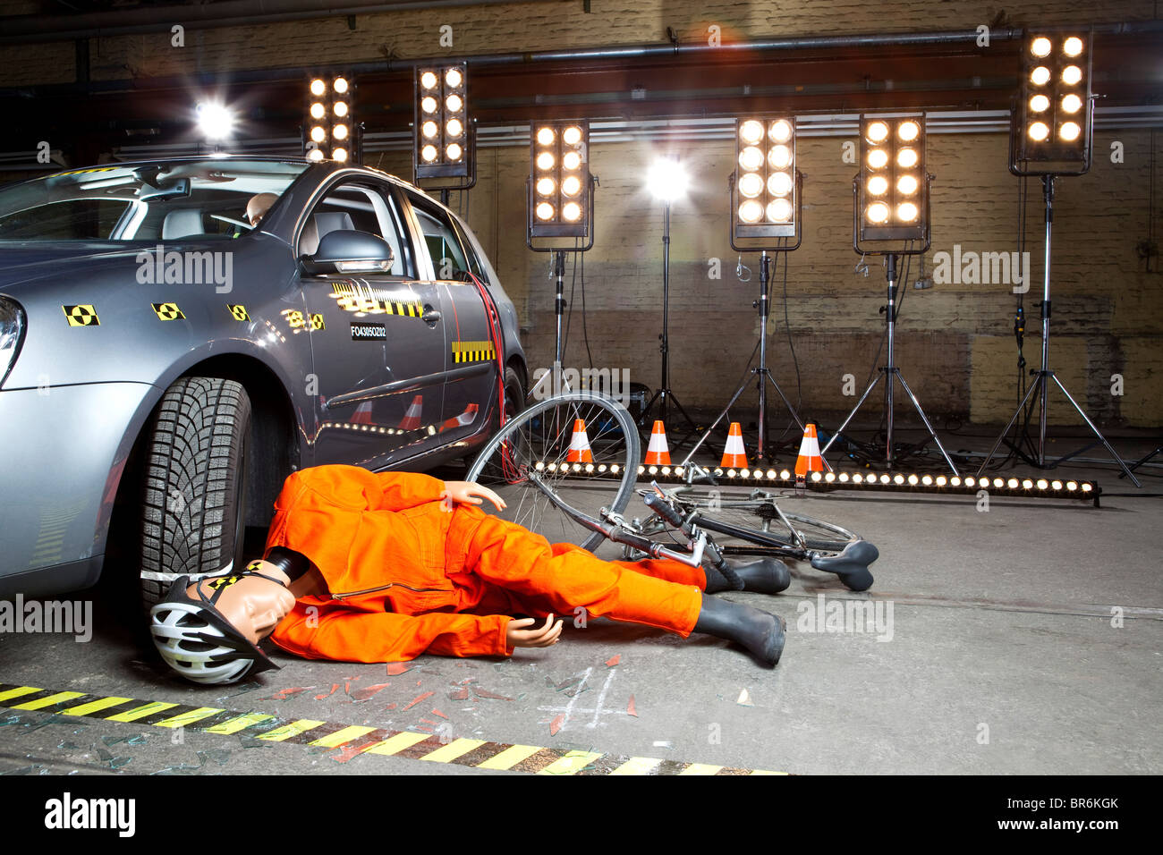 A crash test dummy on ground after scooter crashed into car Stock