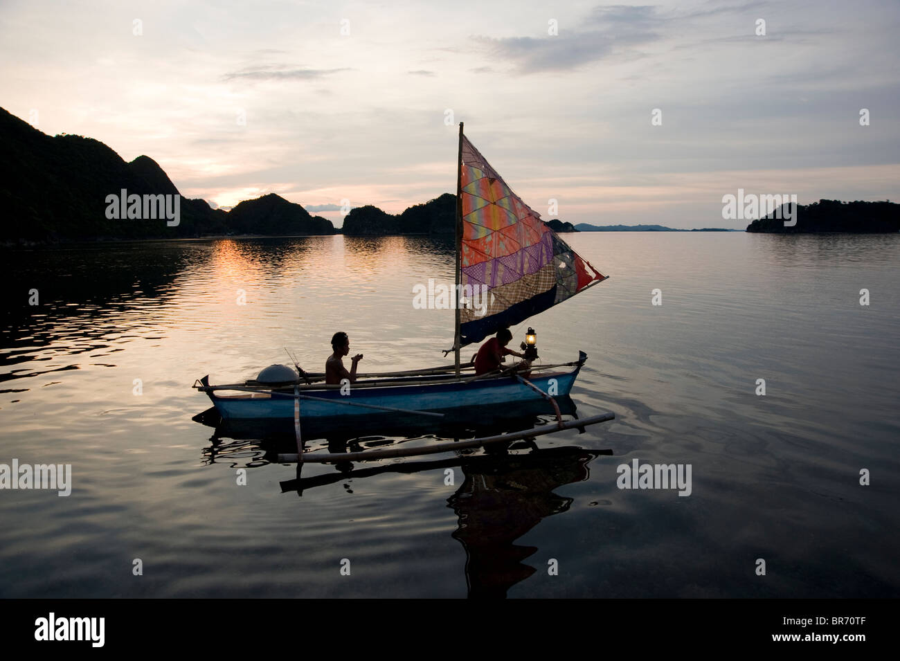 fisherman and son on traditional sailboat out for night fishing, Reel Combo