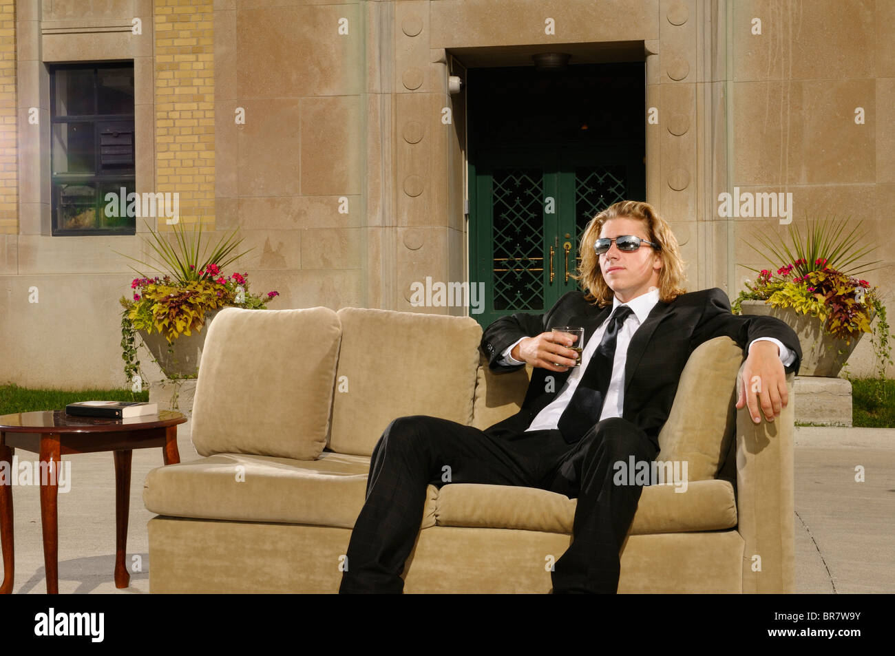 wealthy-young-man-in-suit-sitting-on-a-c