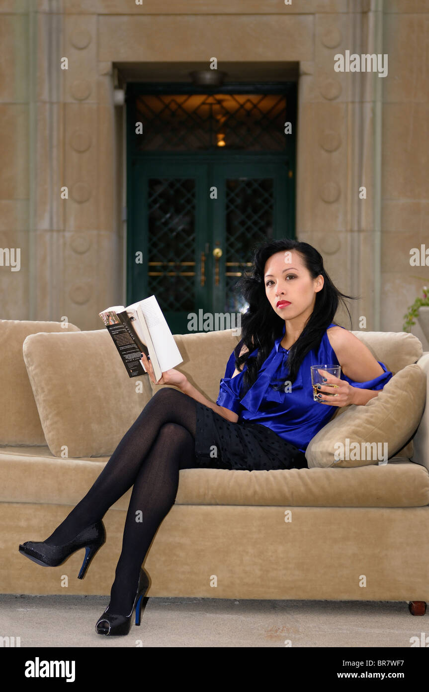 attractive asian woman with crossed legs on a couch