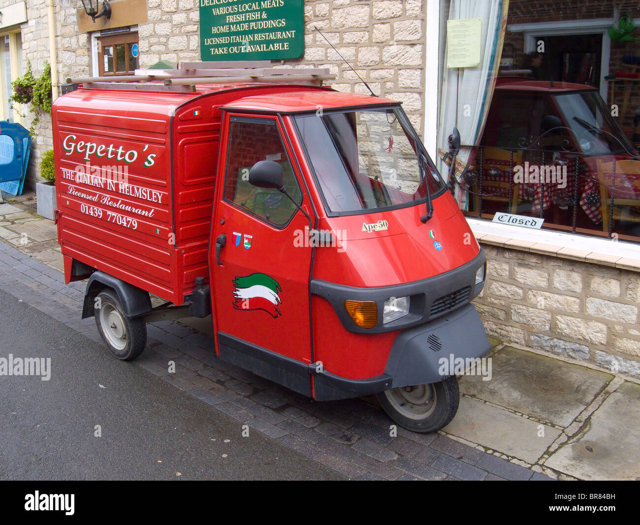 bright red piaggio ape 50 van used by an italian restaurant in stock photo royalty free image. Black Bedroom Furniture Sets. Home Design Ideas