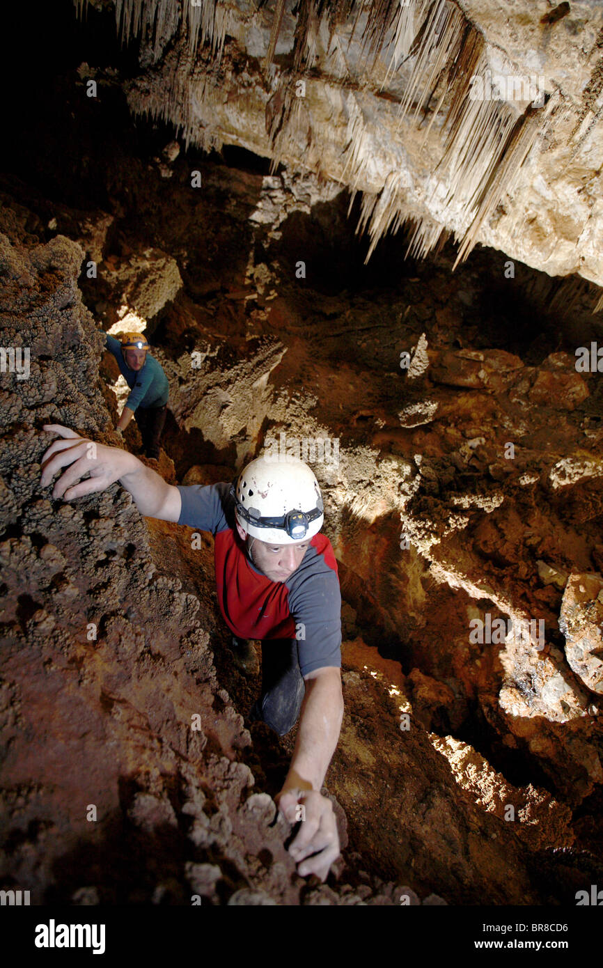 Two Cave Explorers Traverse A Section Of Cave On A Ledge Above A Deep Hole