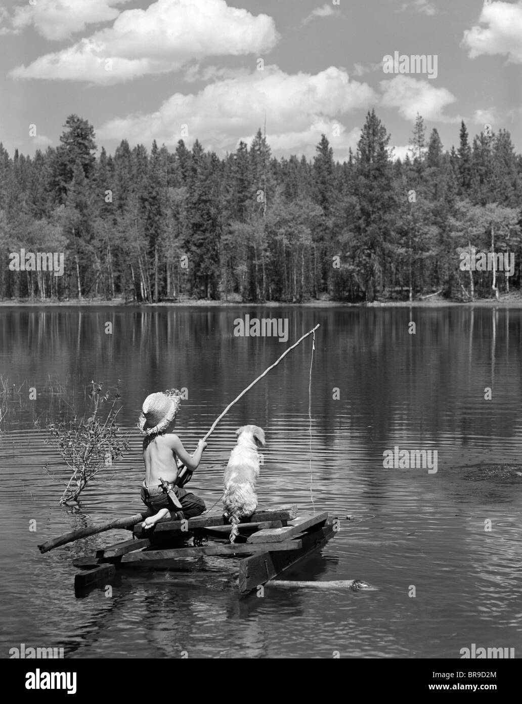 1950s BOY HUCK FINN STYLE ON HOMEMADE RAFT WITH DOG FISHING IN LAKE Stock Photo, Royalty Free ...