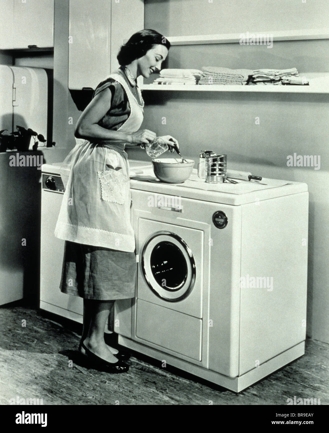 1950s Housewife Using Top Of Washing Machine Dryer As