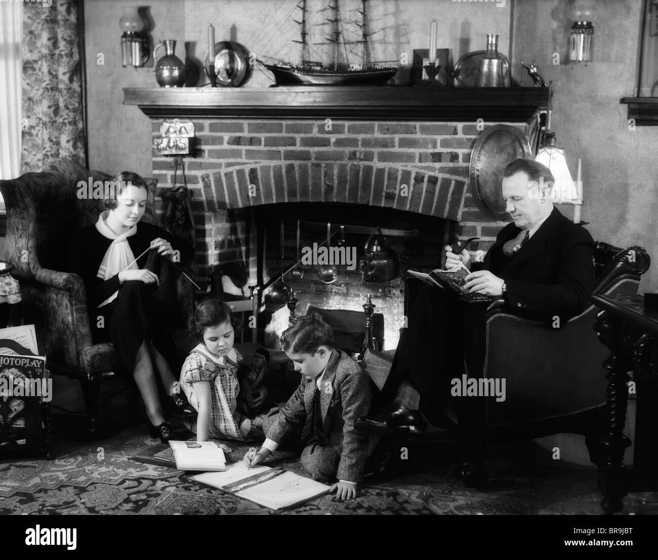 1930s family of four sitting in front fireplace mother knitting