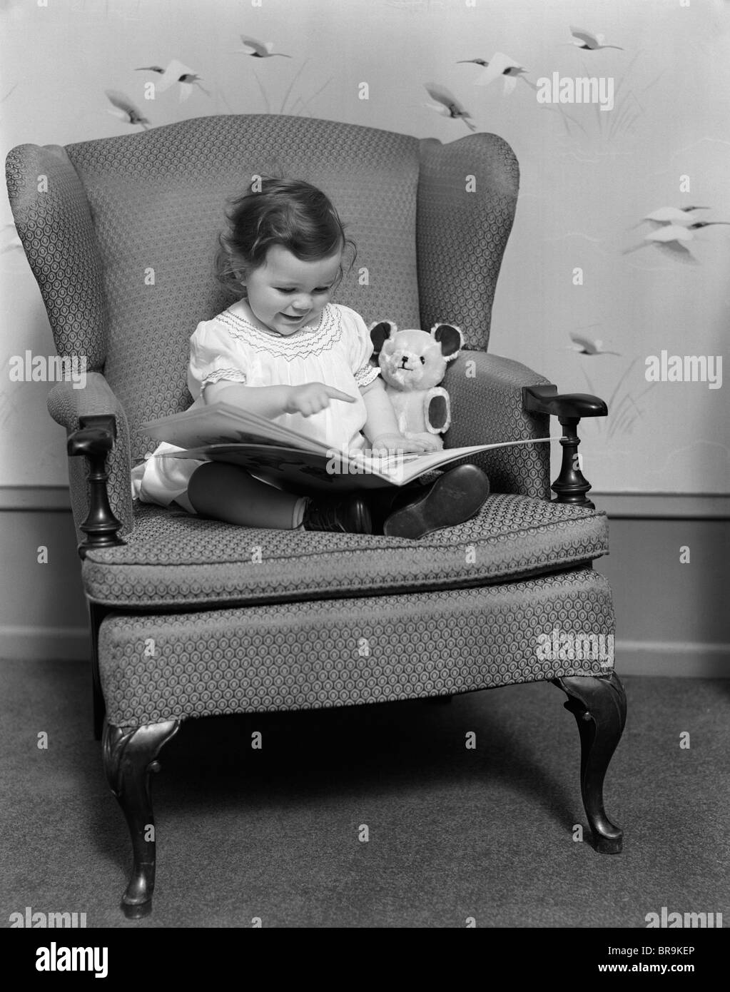 Black child sitting in chair -  1930s Little Girl Child In Large Chair With Bear Reading Book Stock Photo