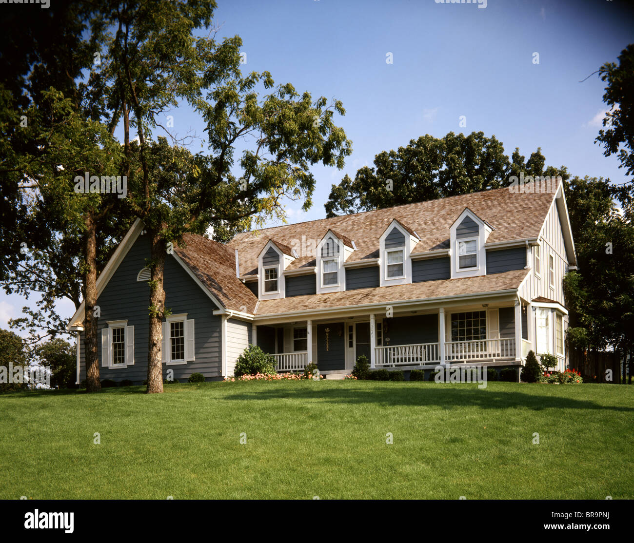 GRAY TWO STORY HOUSE WITH FRONT PORCH FOUR DORMER STYLE WINDOWS