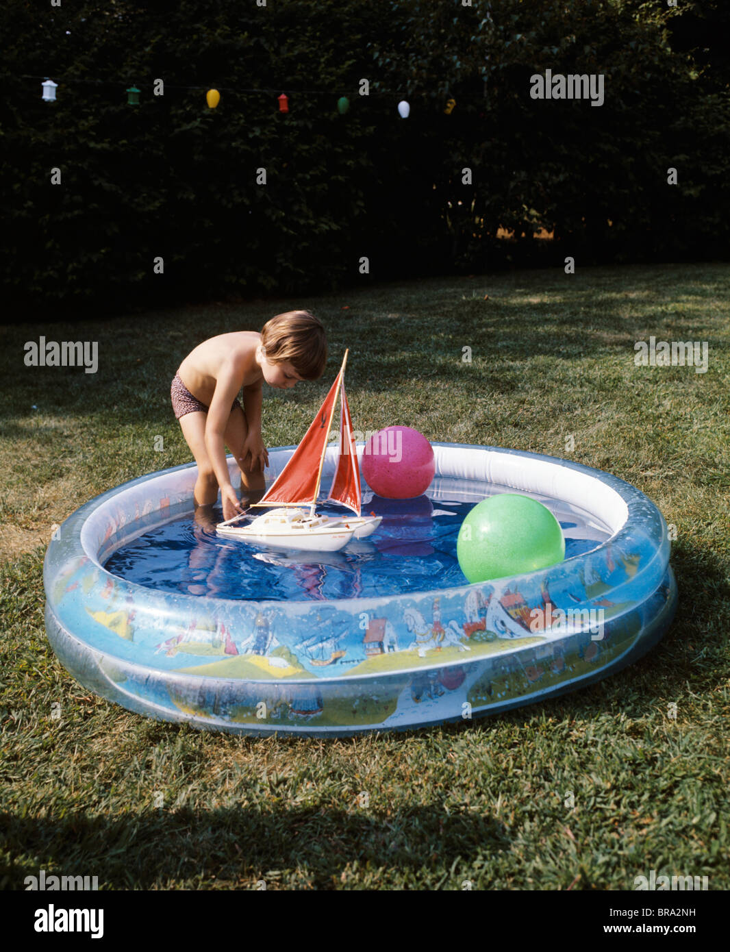1970s boy toddler playing toy boat backyard plastic inflatable