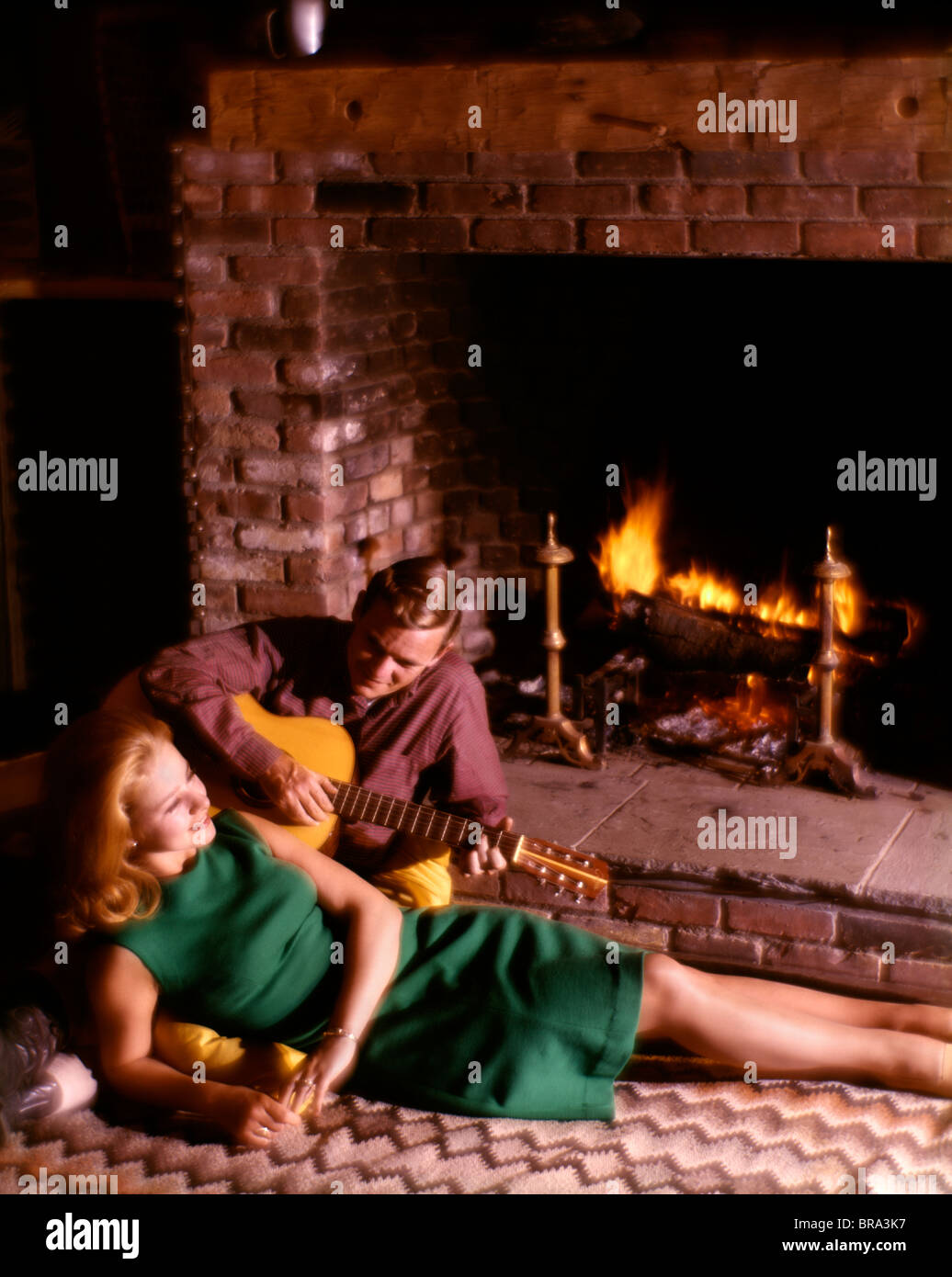 COUPLE MAN WOMAN IN FRONT OF FIREPLACE GUITAR Stock Photo, Royalty ...