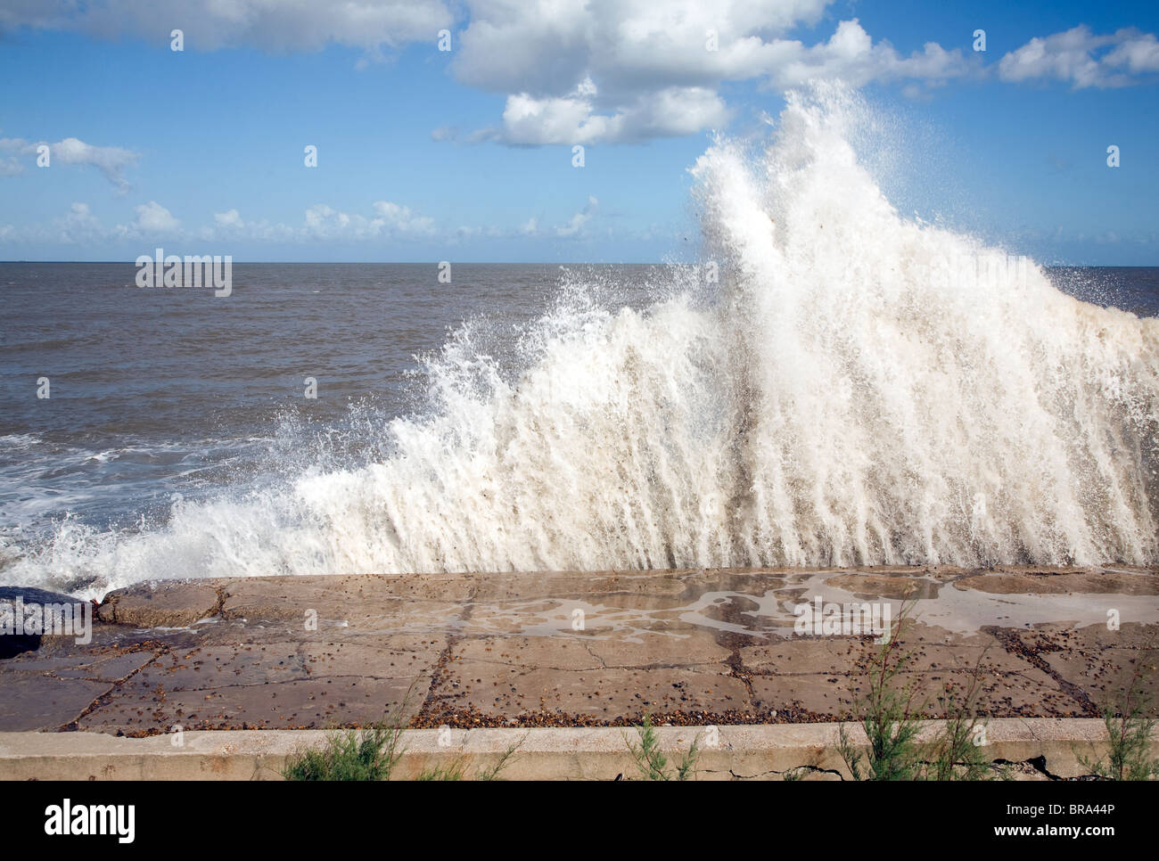 Waves hit sea wall illustrating hydraulic action and ...
