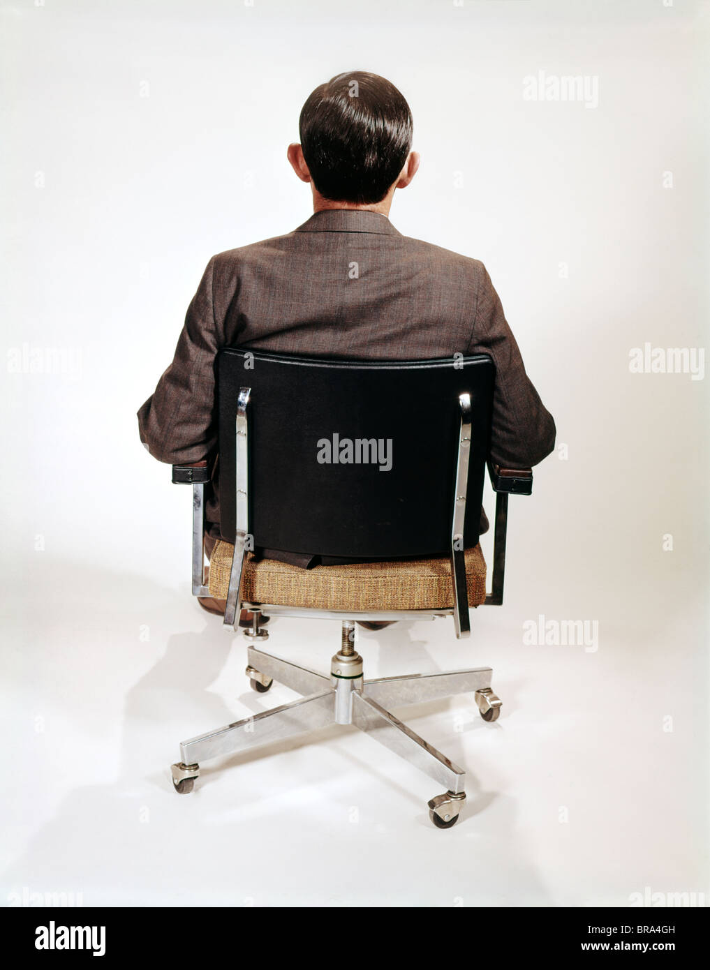 196Os BUSINESS MAN BACK VIEW SITTING IN OFFICE CHAIR RETRO
