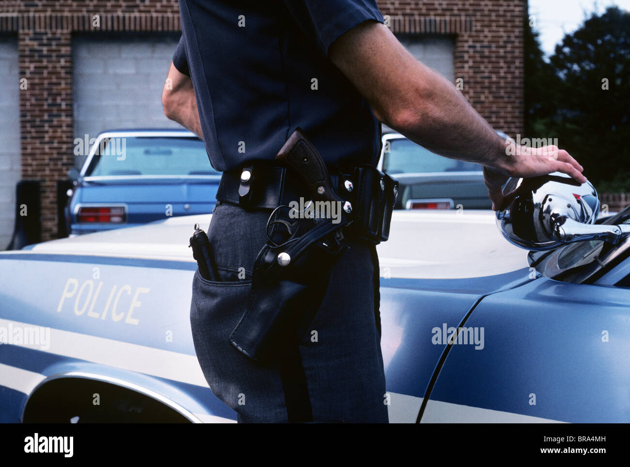 1970s detail of police officers hip with belt gun and holster