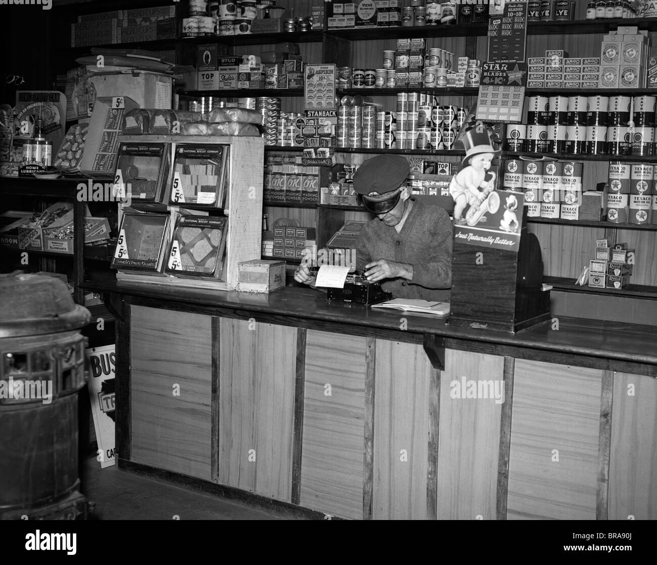 General Store Stock Photos General Store Stock Images: 1930s MAN BEHIND COUNTER IN GENERAL STORE USING TYPEWRITER