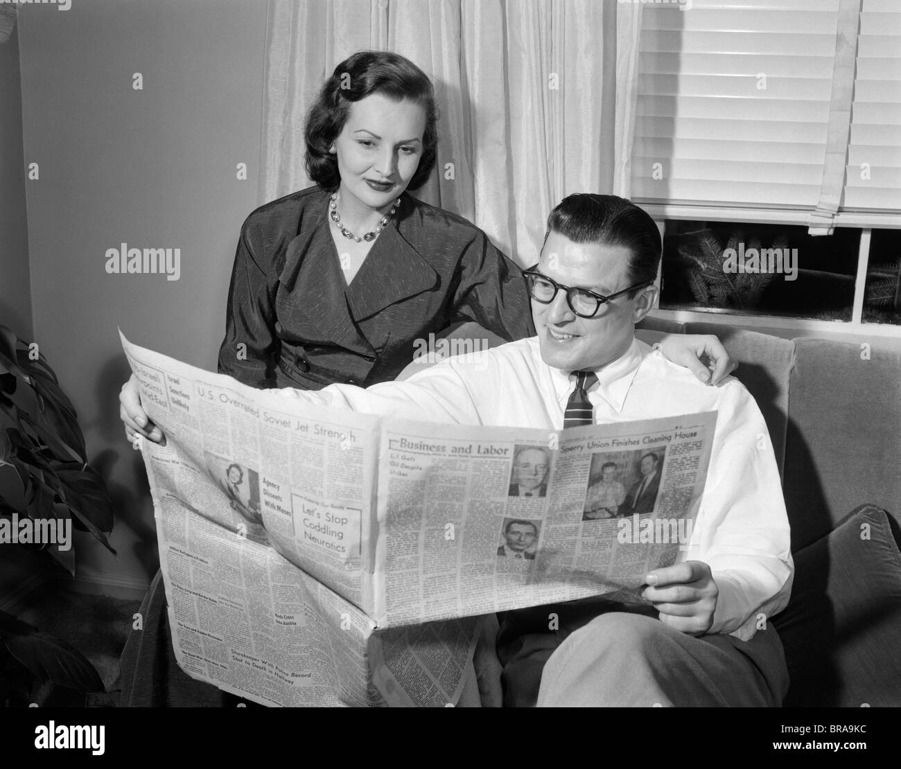 1950s COUPLE MAN WOMAN READING NEWSPAPER Stock Photo ...