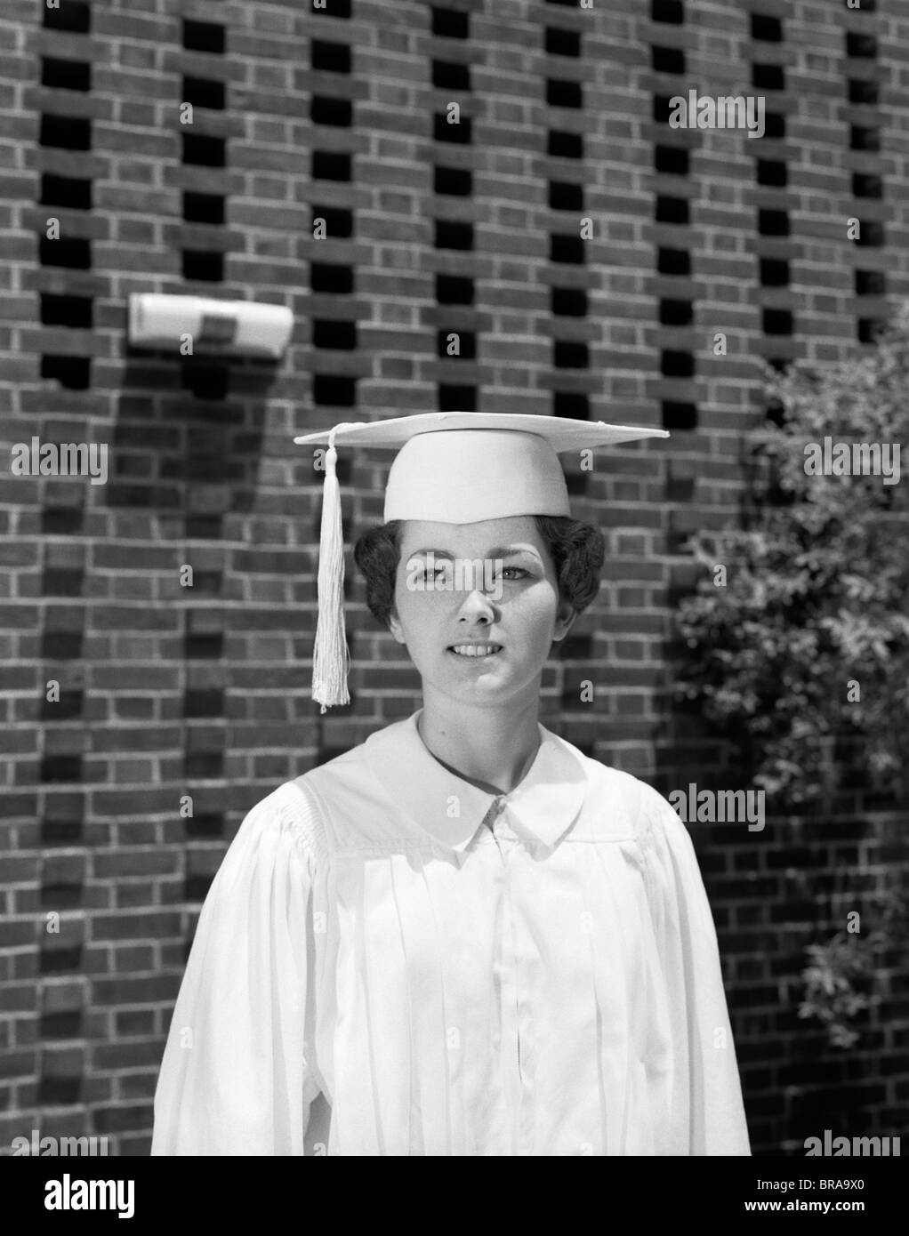 Black dress under white graduation gown - 1960s Portrait Teen Girl White Cap And Gown Graduation Robe Stock Image