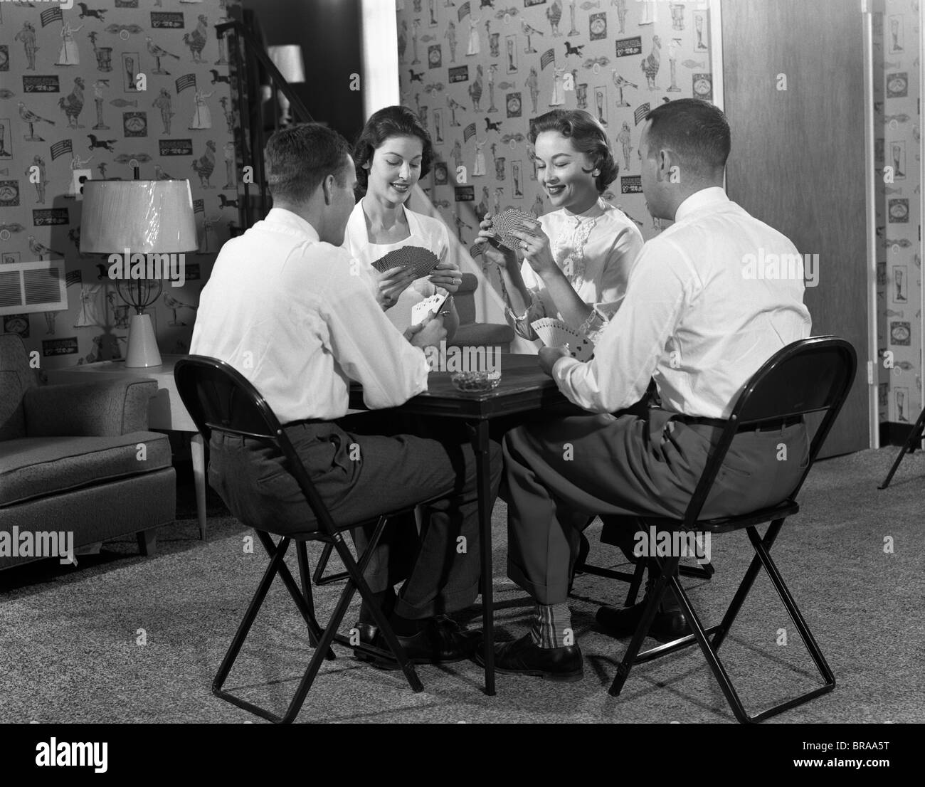 1950s TWO COUPLES SEATED AT FOLDING CARD TABLE PLAYING BRIDGE