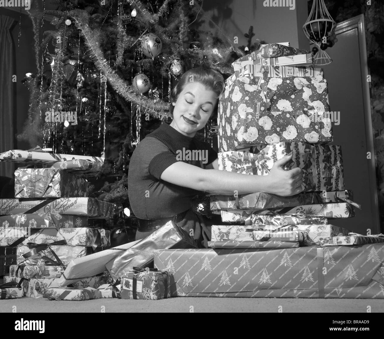 1950s Woman Sitting By Christmas Tree Hugging Pile Of