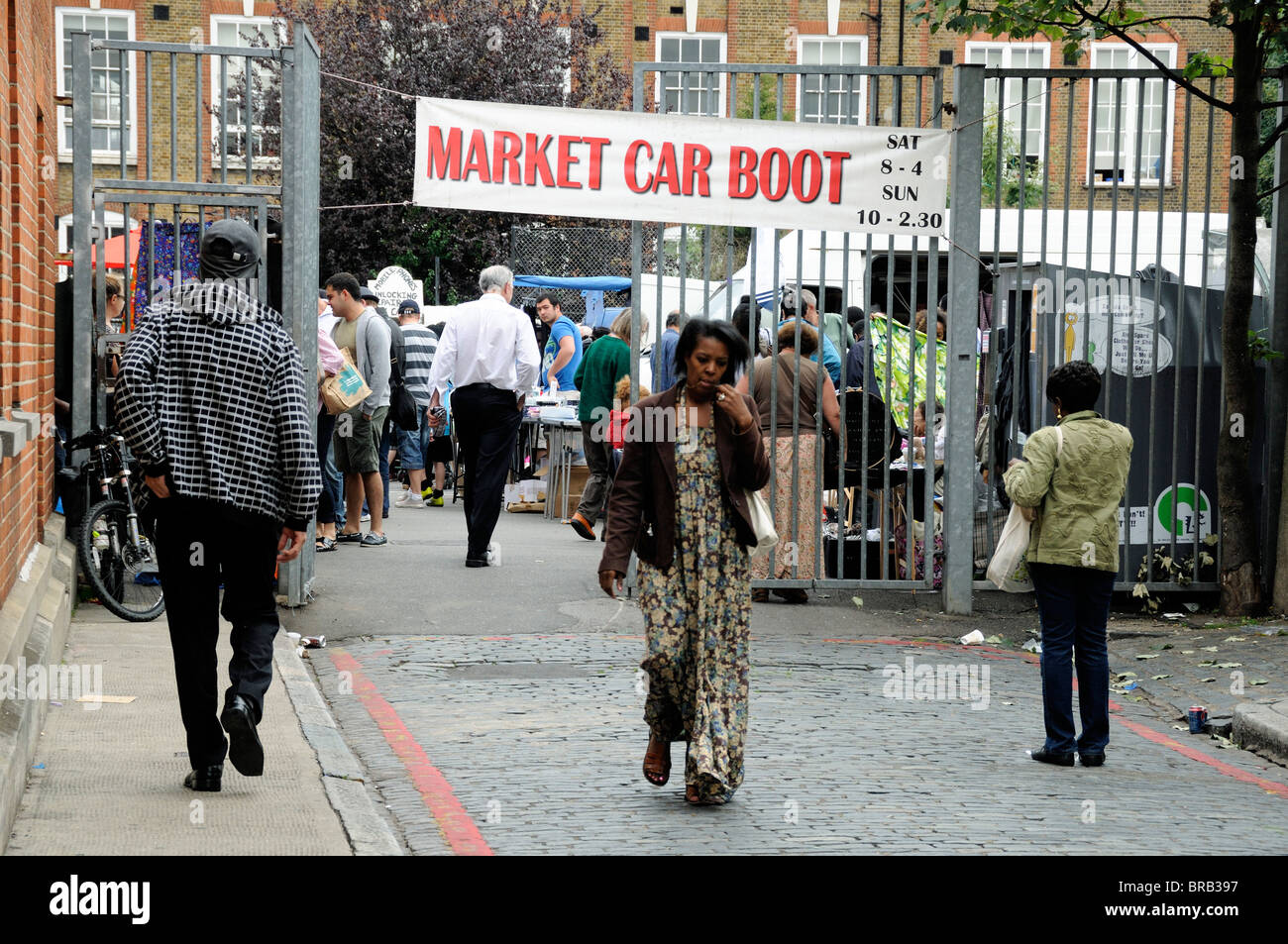 Lady leaving car boot sale holloway london england uk stock image