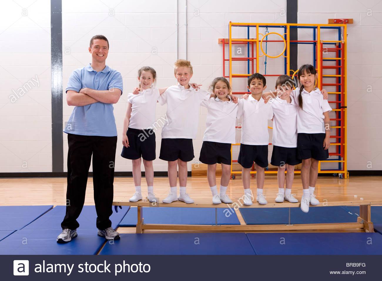 Smiling gym teacher and school children in
