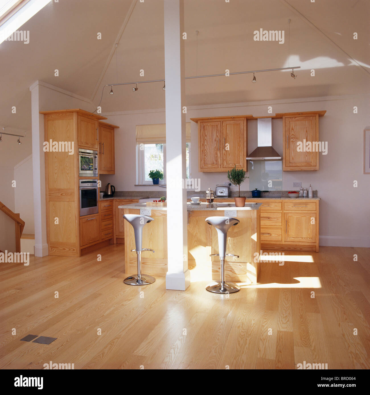 Stock Photo   Wooden Flooring And Apex Ceiling In Modern Loft Conversion  Kitchen With With Pale Wood Fitted Units